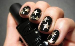 Uñas con manicura de estrellas doradas y fondo negro